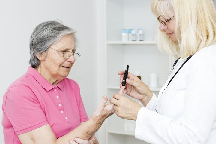 Doctor testing glucose on a patient's finger