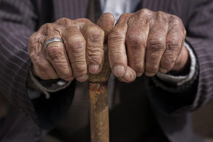 An older man holding a cane