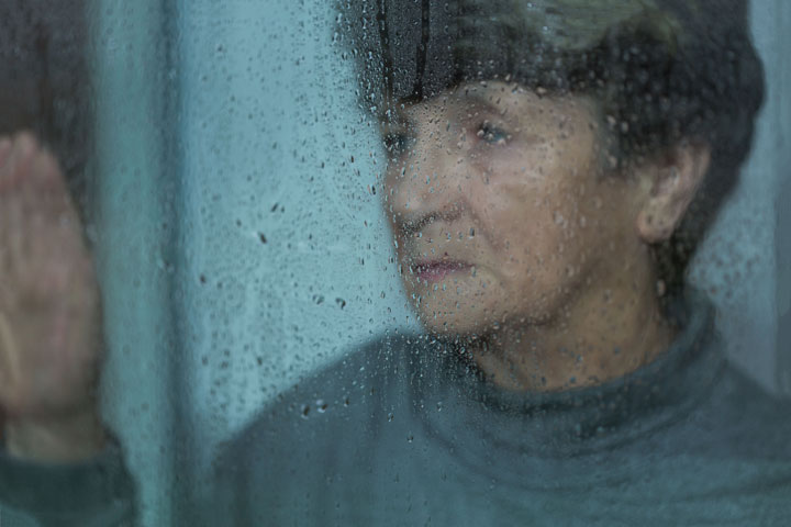 An older lady looking sad and starting out the window at rain drops