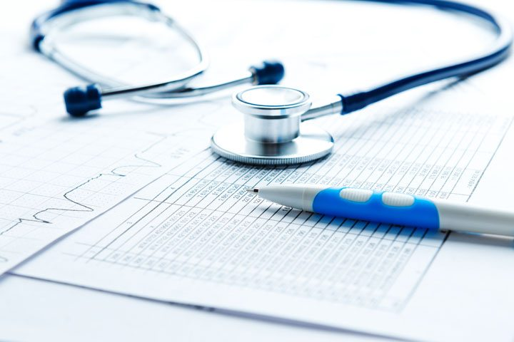 a stethoscope and a pen and medical charts