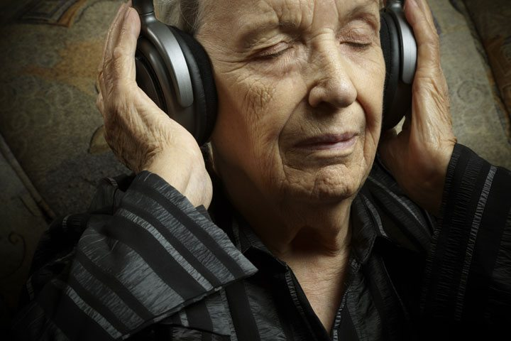 Senior woman listening to music on headphones with her eyes closed