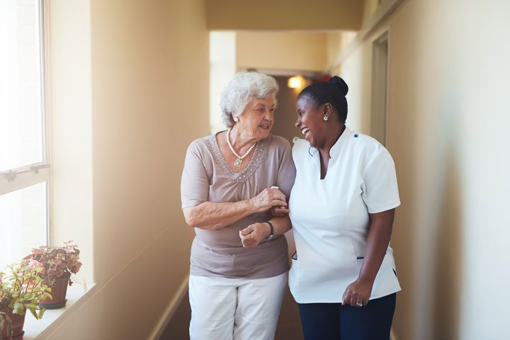Happy female caregiver and senior woman walking together F
