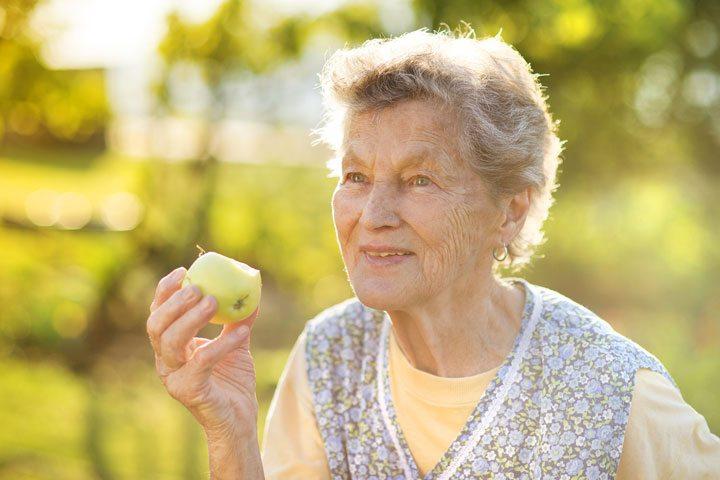 senior woman eating an apple