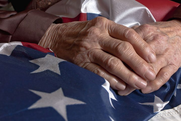 A seniors' hands atop an American flag