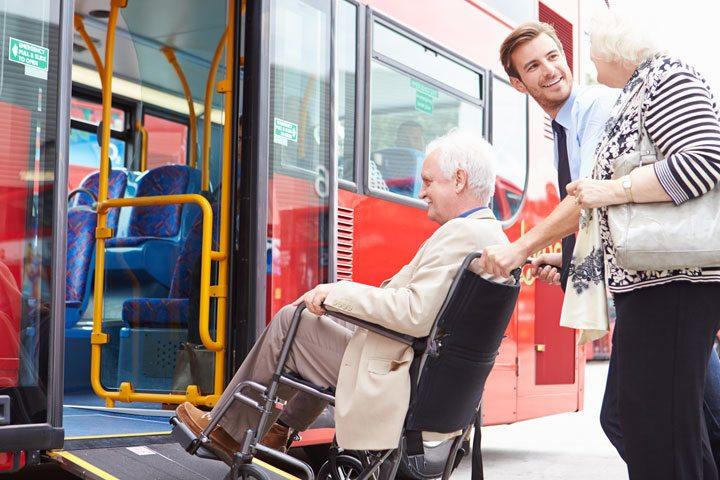 Driver Helping Senior Couple Board Bus Via Wheelchair Ramp