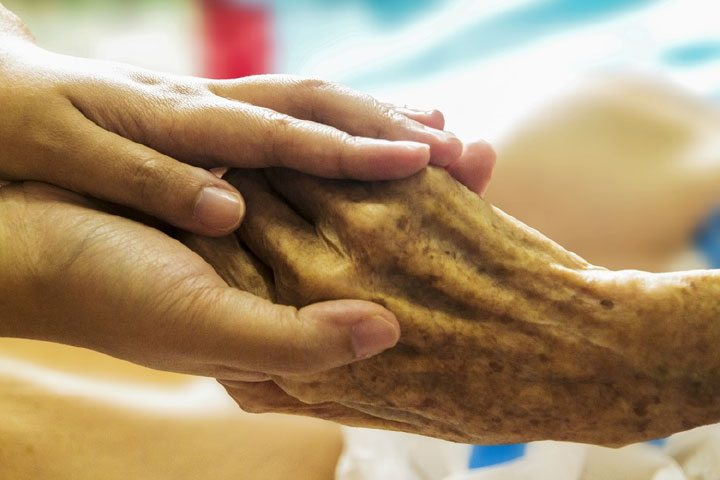 Young hand holding older person's hand