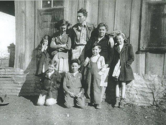 The photo of the family in front of the shack is my momma's family. She is the little girl standing to the far right.