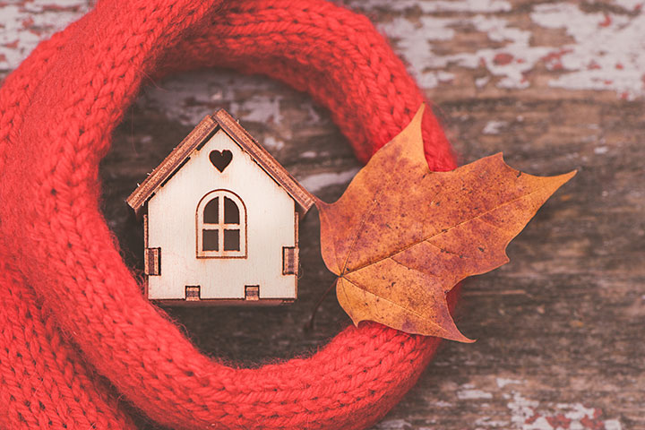 toy house is wrapped in a warm scarf with an autumn leaf. The concept is warm, cozy, loving, protecting the house.