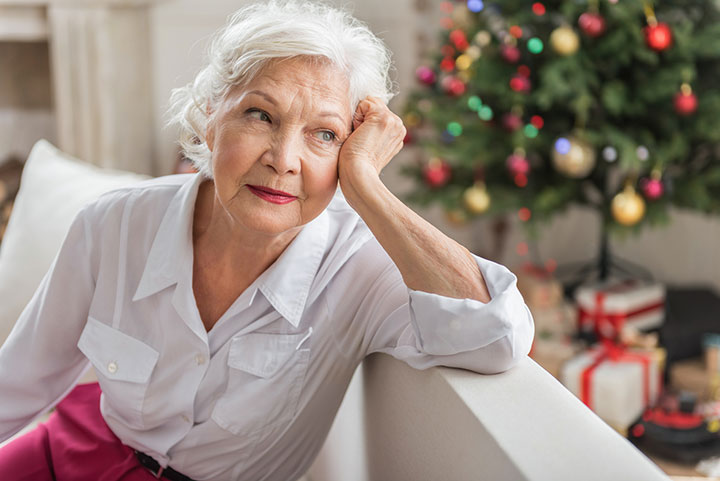 Charming sad old woman is sitting on sofa